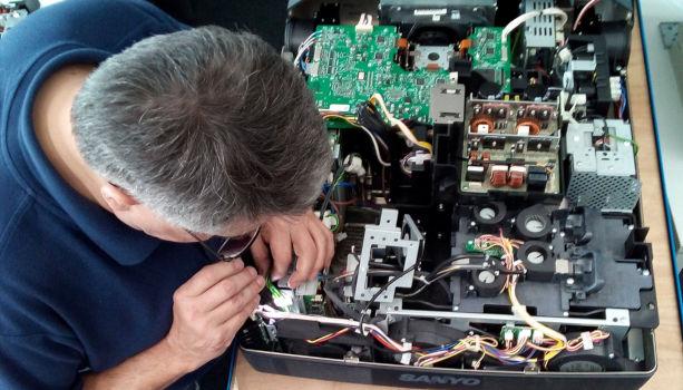 Techniker von Beamer-Reparatur bei der Arbeit